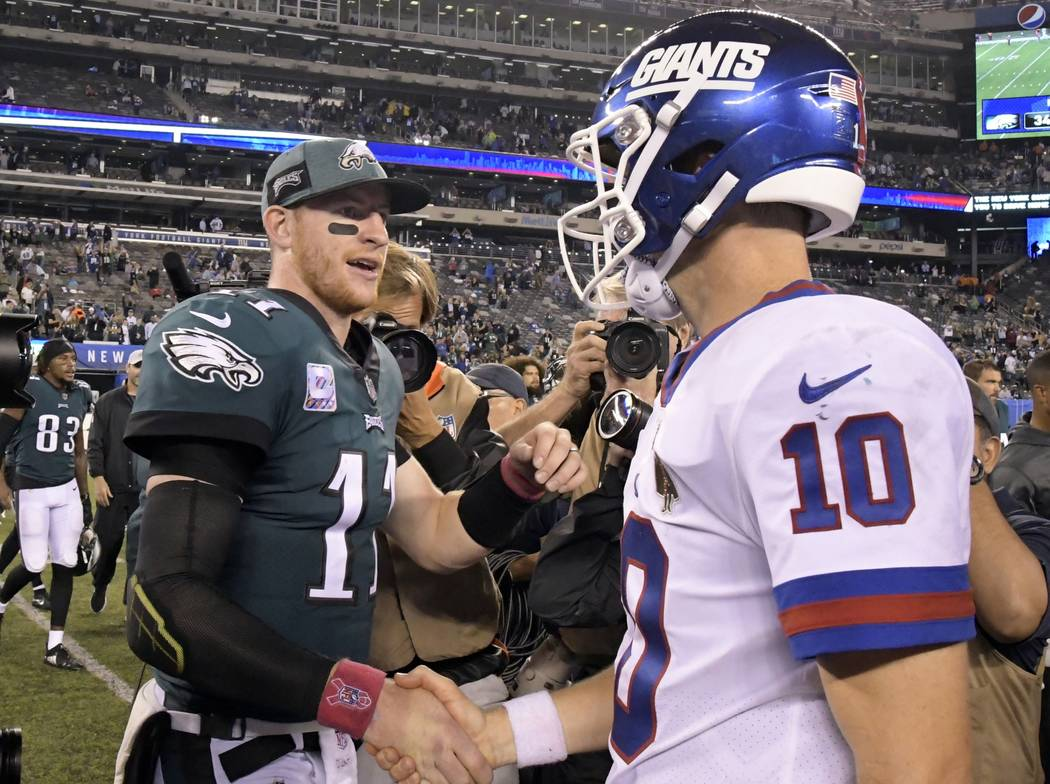 Philadelphia Eagles quarterback Carson Wentz (11) shakes hands with New York Giants quarterback Eli Manning (10) after an NFL football game Thursday, Oct. 11, 2018, in East Rutherford, N.J. The Ea ...