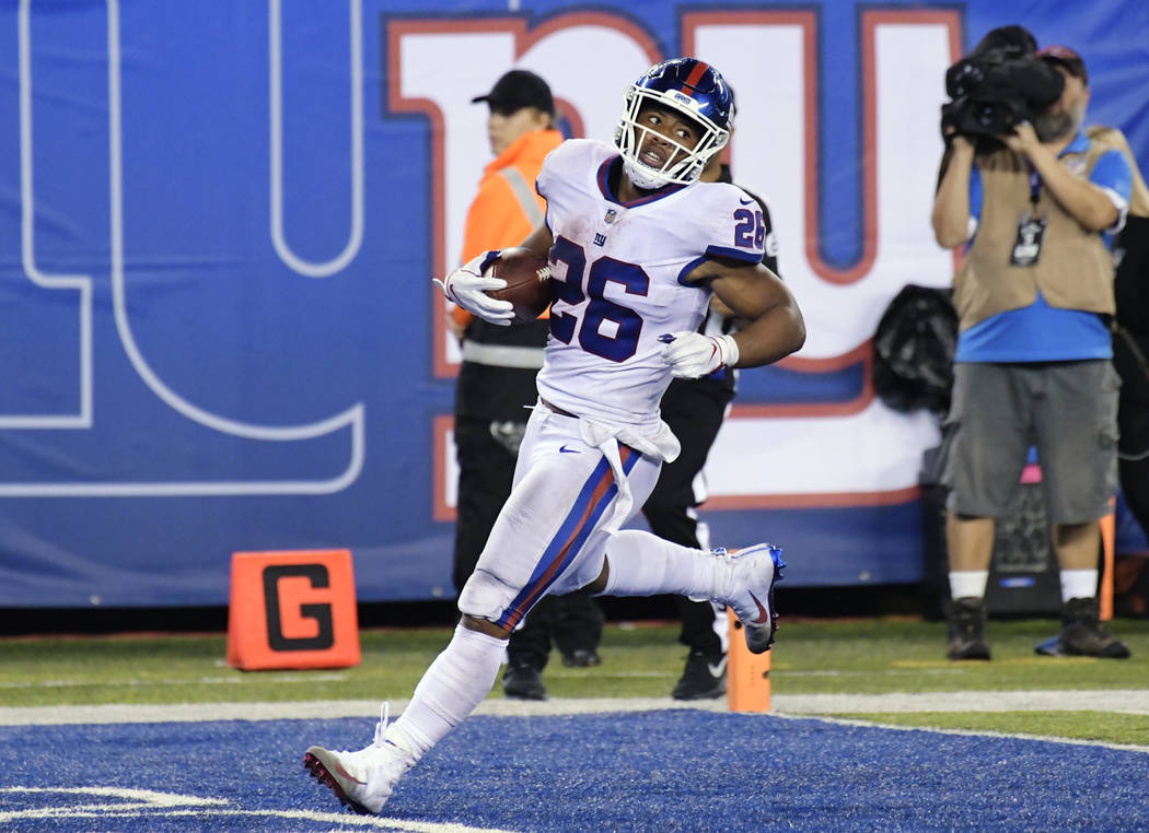 New York Giants running back Saquon Barkley runs in for a touchdown during the second half of the team's NFL football game against the Philadelphia Eagles on Thursday, Oct. 11, 2018, in East Ruthe ...