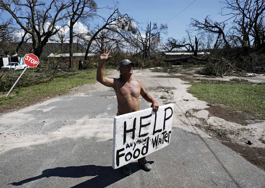 Michael Williams, 70, waves to passing motorists while looking for food and water as downed trees prevent him from driving out of his damaged home with his family in the aftermath of Hurricane Mic ...