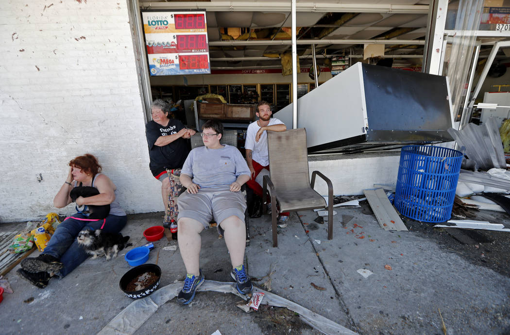 Dawn Vickers, left, her mother Patsy Vickers, son Ryder Vickers, and friend Robert Brock, right, who rode out Hurricane Michael in their now-destroyed home, sit in front of a damaged convenience s ...