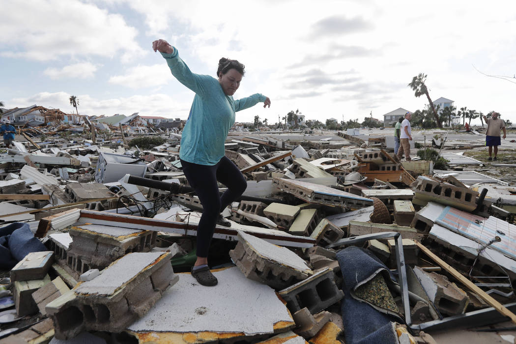 Mishelle McPherson, climbs over the rubble of the home of her friend as she searches for her, since she knows she stayed behind in the home during Hurricane Michael, in Mexico Beach, Fla., Thursda ...