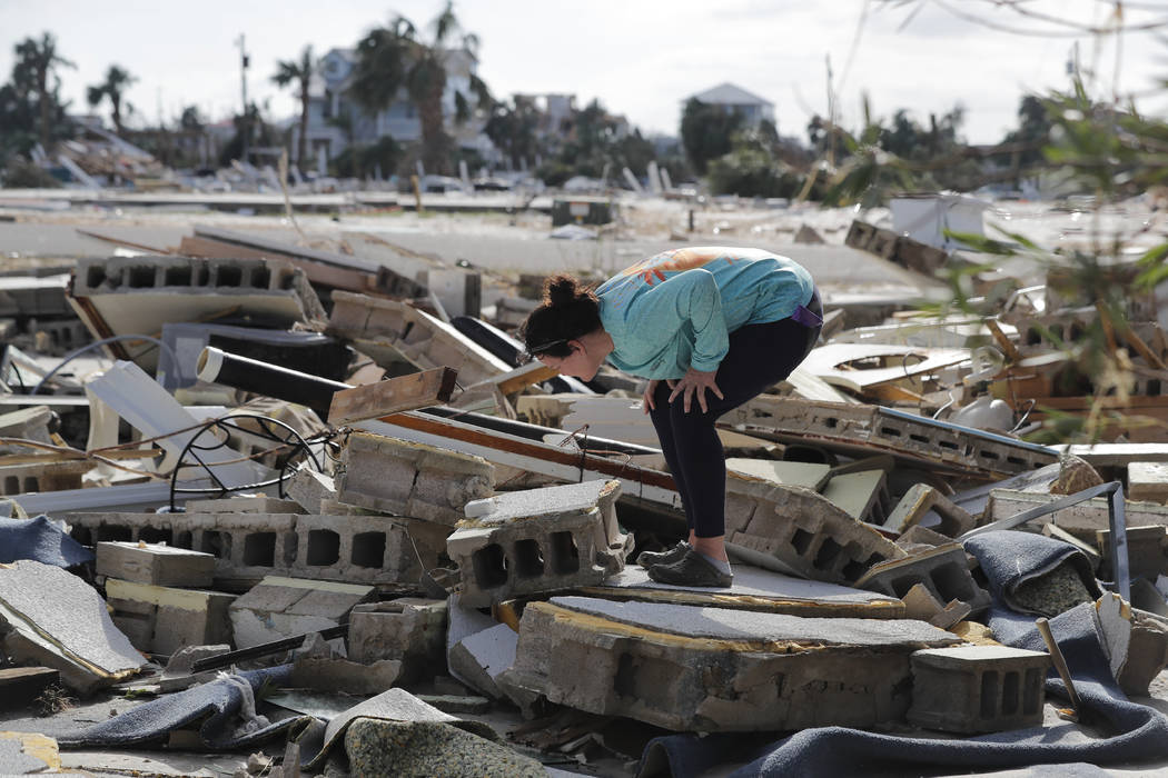 Mishelle McPherson looks for her friend in the rubble of her home, since she knows she stayed behind in the home during Hurricane Michael, in Mexico Beach, Fla., Thursday, Oct. 11, 2018. (AP Photo ...