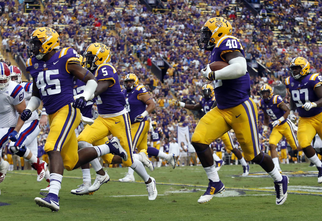 FILE - In this Saturday, Sept. 22, 2018, file photo, LSU linebacker Devin White (40) returns a fumble in the first half of an NCAA college football game against Louisiana Tech in Baton Rouge, La. ...