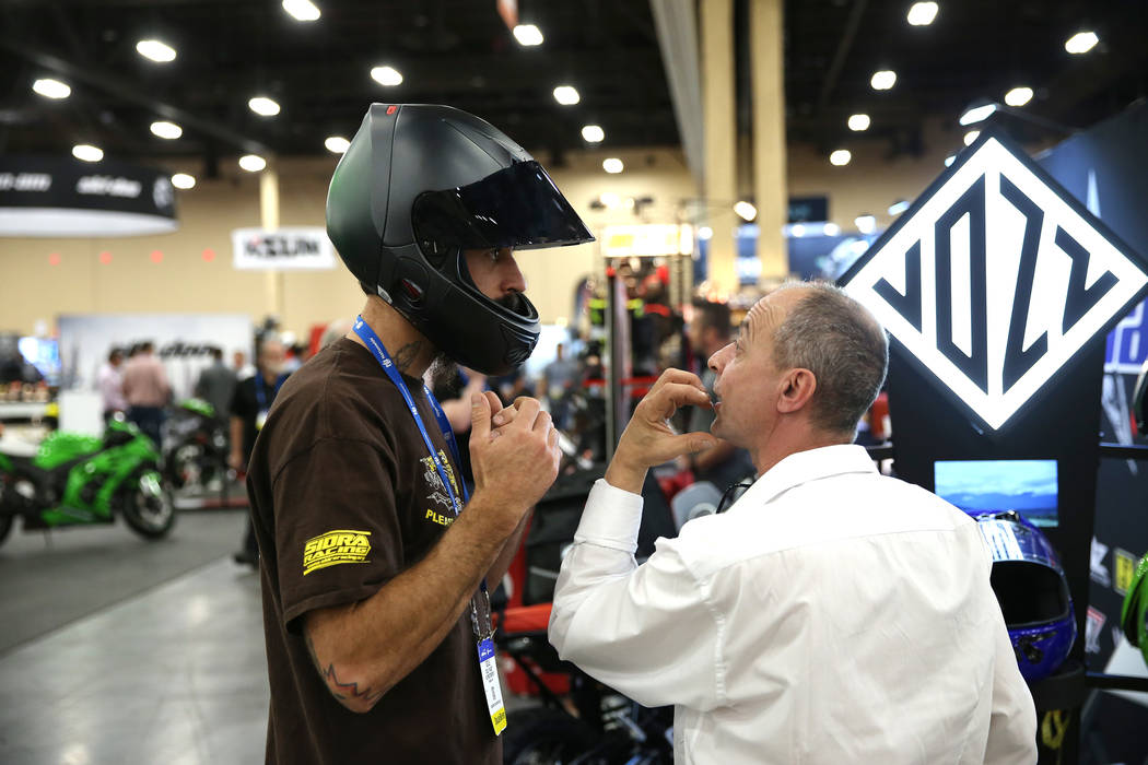 John Vozzo, right, inventor of Vozz Helmets, shows a helmet to Courtney Rich of Boise, Idaho, during the American Motorcycle International Expo at the Mandalay Bay Convention Center in Las Vegas, ...