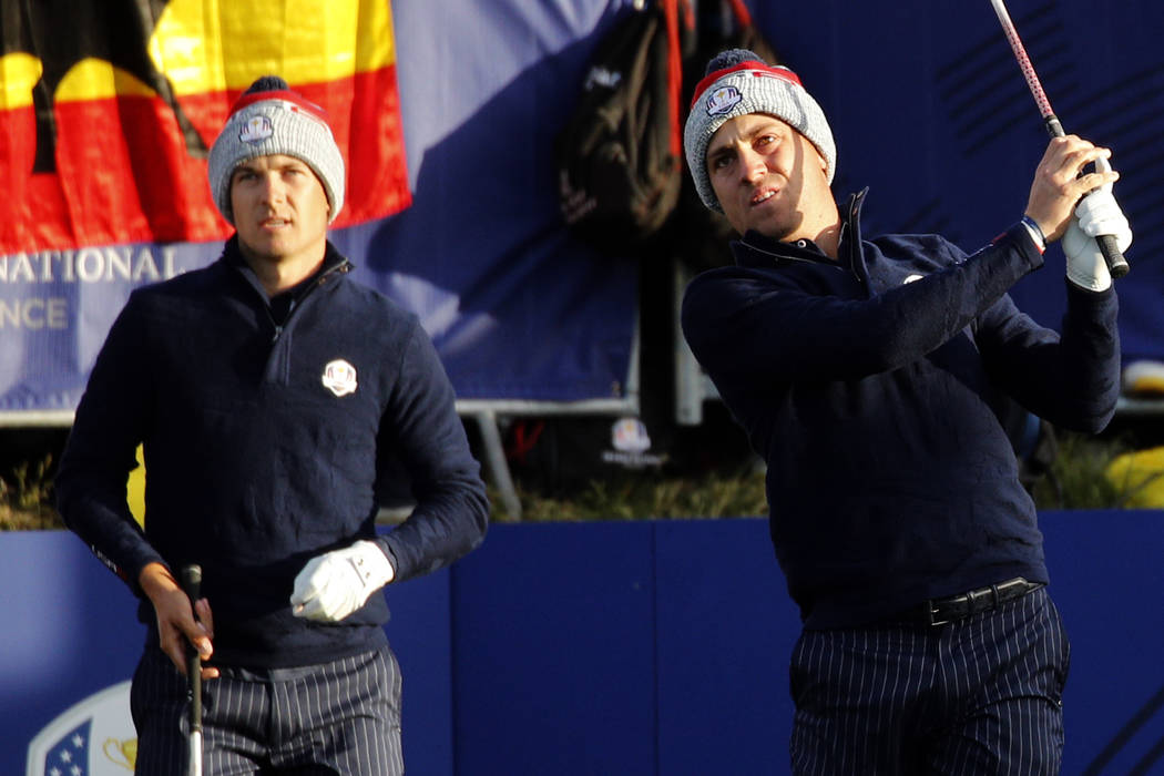 Justin Thomas of the US follows his shot from the first tee while his teammate Jordan Spieth looks on during their fourball match on the second day of the 42nd Ryder Cup at Le Golf National in Sai ...