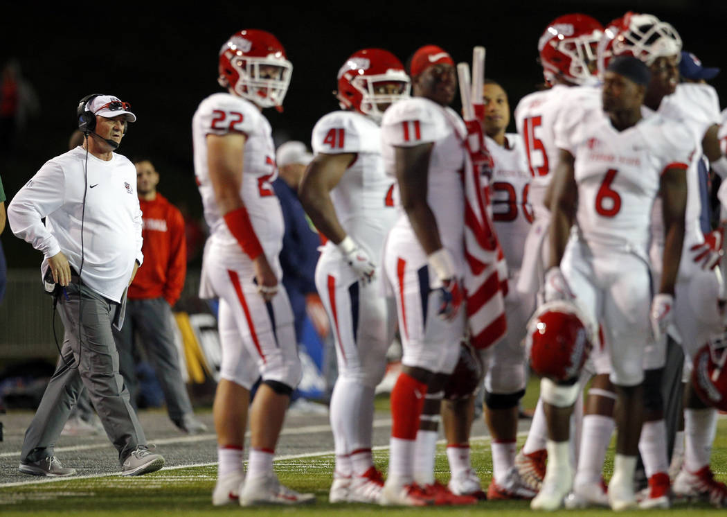 Fresno State coach Jeff Tedford, far left, approaches his players during a timeout in the first half of an NCAA college football game against New Mexico in Albuquerque, N.M., Saturday, Oct. 20, 20 ...