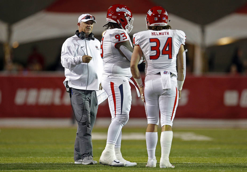 Fresno State coach Jeff Tedford, left, talks to linebacker George Helmuth (34) and defensive tackle Jasad Haynes (93) during a timeout in the first half of an NCAA college football game against Ne ...