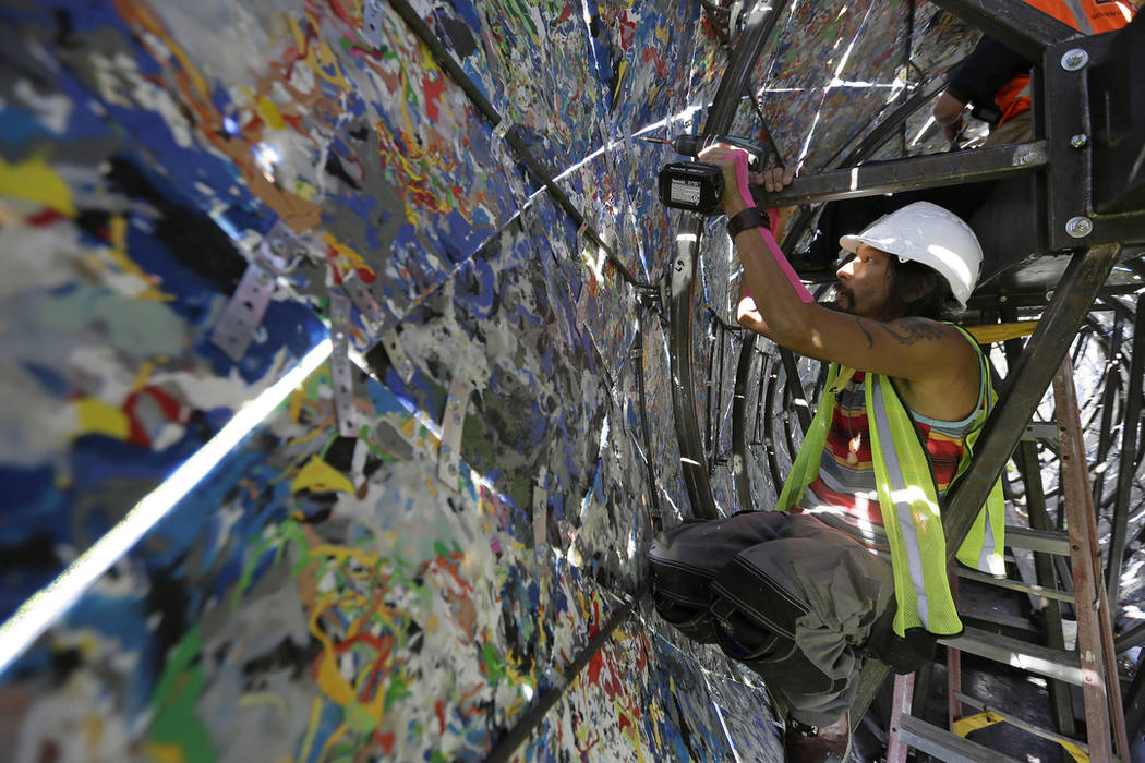 Jared Chen works at reinforcing panels inside a blue whale art piece made from discarded single-use plastic at Crissy Field Friday, Oct. 12, 2018, in San Francisco. (AP Photo/Eric Risberg)