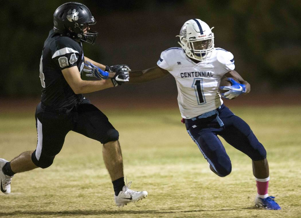 Centennial running back Jordan Smith (1) carries the ball past Palo Verde Linebacker Bogdan Filipovic (84) during the first half of a varsity football game at Palo Verde High School in Las Vegas o ...