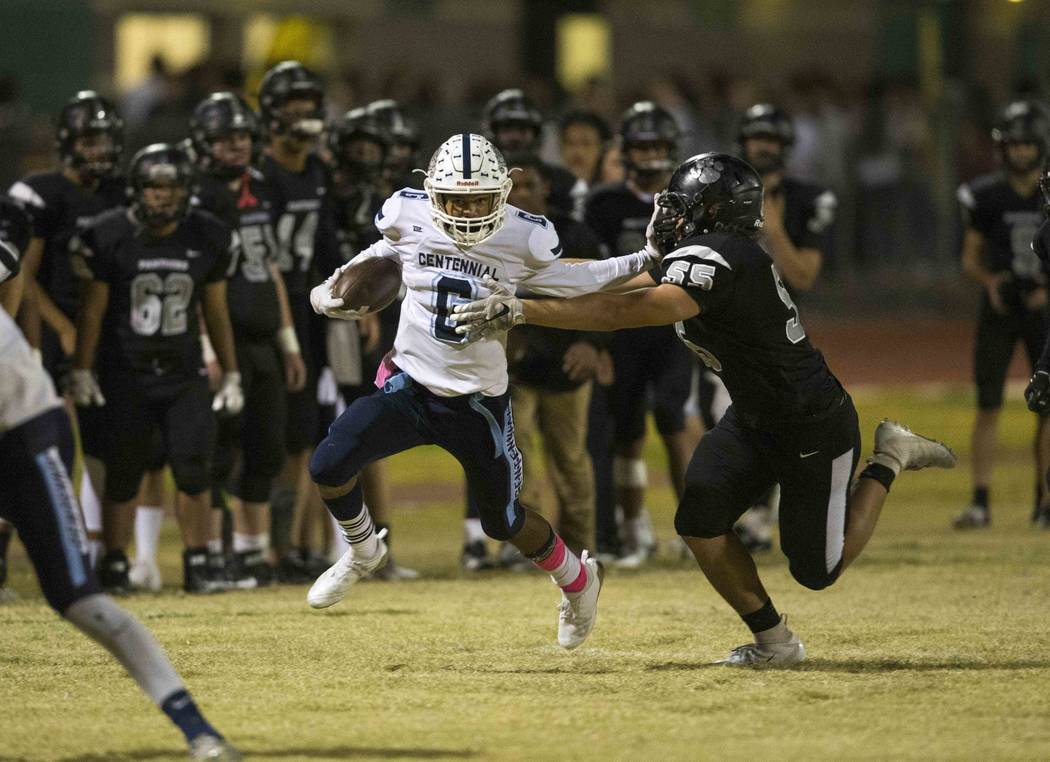 Centennial's Gerick Robinson (6) stiff arms Palo Verde's Trent Ausbon (55) as he carries the ball during the second half of a varsity football game at Palo Verde High School in Las Vegas on Friday ...
