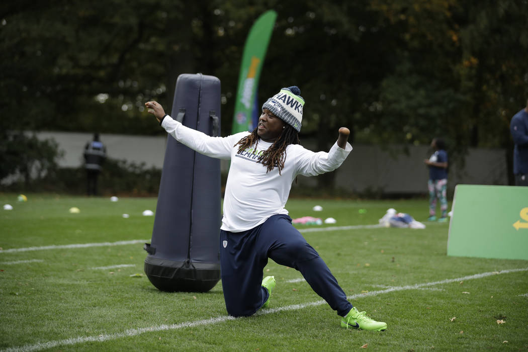 Seattle Seahawks' linebacker Shaquem Griffin, whose hand was amputated when he was four years old, takes part in an NFL flag event with London schoolchildren after a training session at the Grove ...