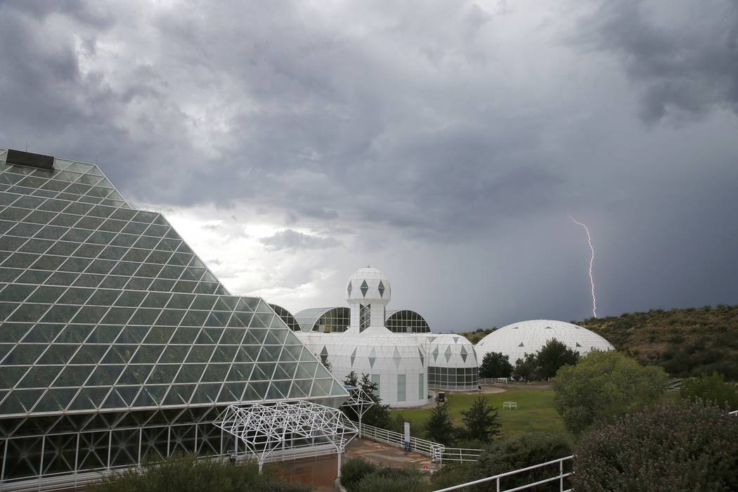 Several of the main buildings of the Biosphere 2 complex, including the tropical rainforest, left, the technosphere, middle, and the south lung, right, are shown as a thunderstorm moves past, in O ...