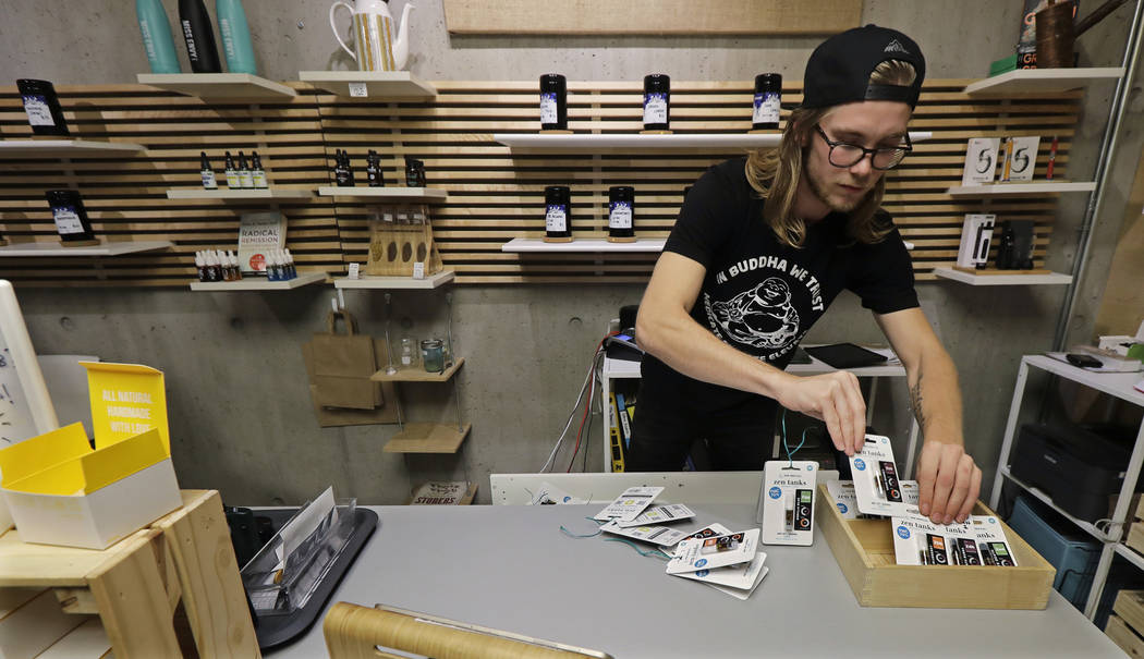 Peter Backlund, an employee at the Village Bloomery medical cannabis dispensary in Vancouver, British Columbia, organizes a display in September. (AP Photo/Ted S. Warren)