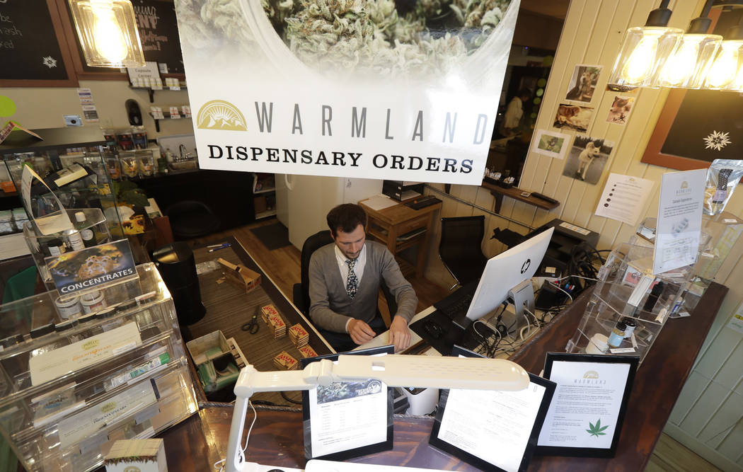 Bud tender Dave Chelli works at the Warmland Centre, a medical marijuana dispensary in Mill Bay, British Columbia, on Vancouver Island in September. (AP Photo/Ted S. Warren)