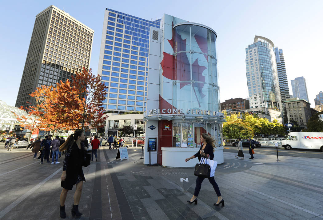 Visitors walk near Canada Place, a tourism and convention center in Vancouver, British Columbia, in September. (AP Photo/Ted S. Warren)