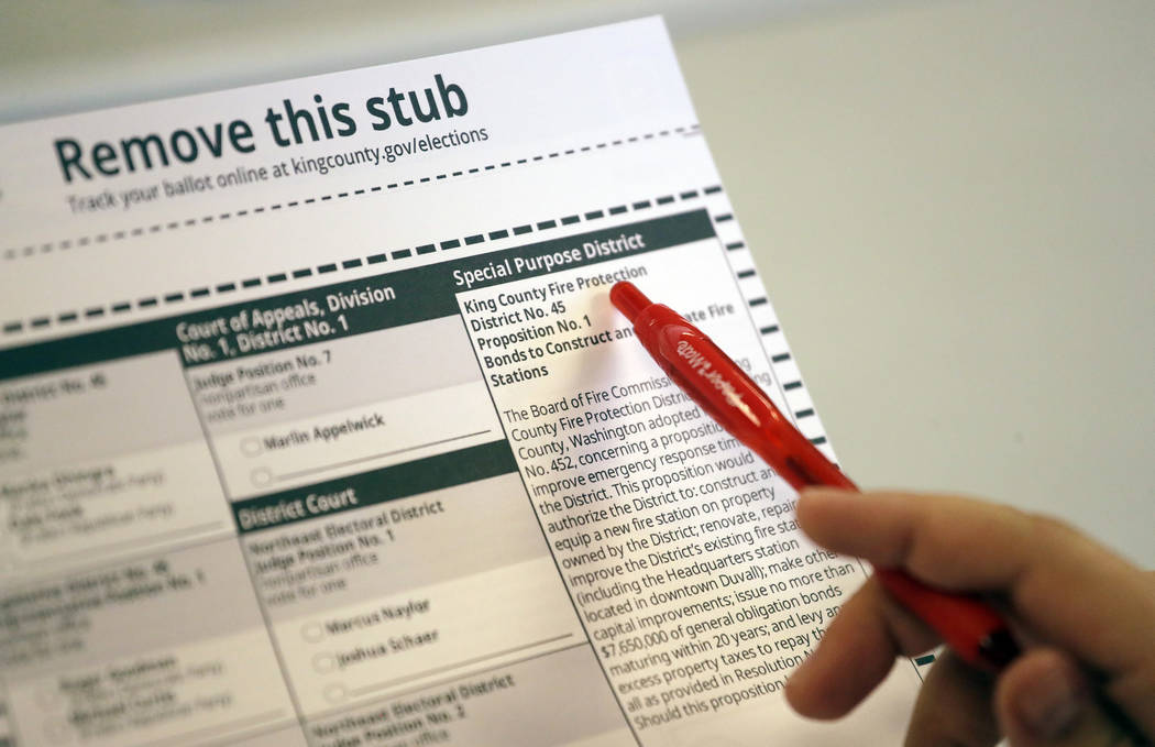 An election supervisor reviews the final proof for the general election ballot at the King County Elections office in Renton, Wash., in September 2018. (AP Photo/Elaine Thompson)