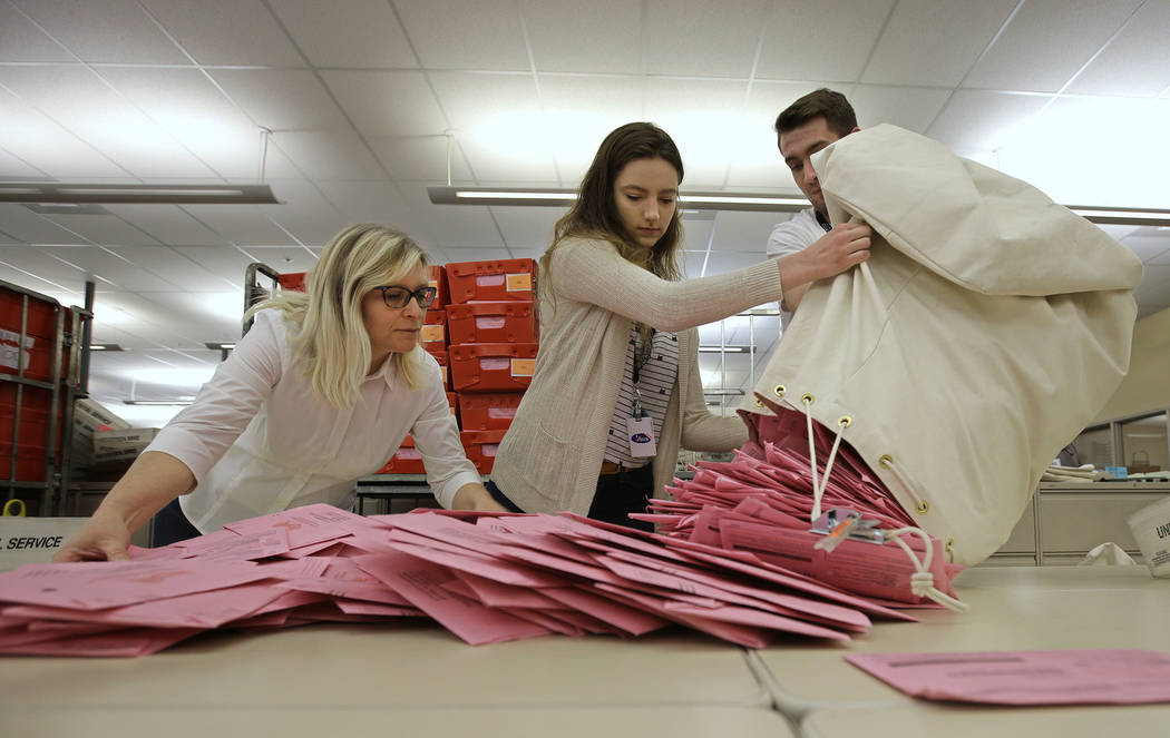 Election workers Heidi McGettigan, left, Margaret Wohlford, center, and David Jensen, unload a bag of ballots brought in a from a polling precinct to the Sacramento County Registrar of Voters offi ...