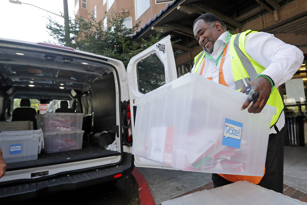 King County Election official Joseph Emanuel loads ballots into a van after collecting them from a drop box in Seattle in August 2018. (AP Photo/Elaine Thompson, File)
