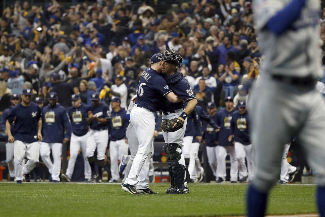 Milwaukee Brewers relief pitcher Corey Knebel (46) and catcher Erik Kratz celebrate after Game 1 of the National League Championship Series baseball game against the Los Angeles Dodgers Friday, Oc ...