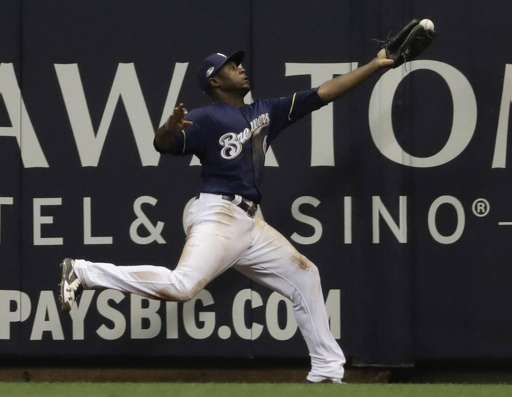Milwaukee Brewers' Lorenzo Cain can't catch a ball hit by Los Angeles Dodgers' Chris Taylor during the ninth inning of Game 1 of the National League Championship Series baseball game Friday, Oct. ...