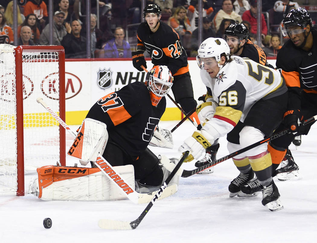Philadelphia Flyers' goaltender Brian Elliott (37) looks for the puck as Vegas Golden Knights' Erik Haula (56) is defended by Wayne Simmonds during the third period of an NHL hockey game, Saturday ...