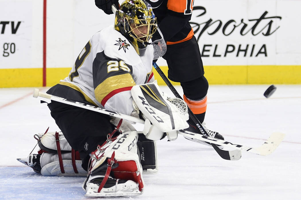 Vegas Golden Knights' goaltender Marc-Andre Fleury makes a save as Philadelphia Flyers' Sean Couturier, rear, looks for a rebound during the second period of an NHL hockey game, Saturday, Oct. 13, ...