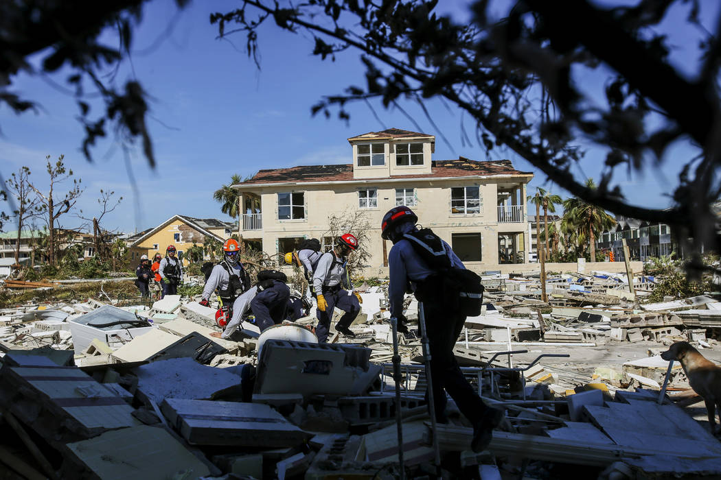 Members from South Florida Task Force search a flattened home destroyed by Hurricane Michael in Mexico Beach, Fla., Friday, Oct. 12, 2018, after Hurricane Michael went through the area on Wednesda ...