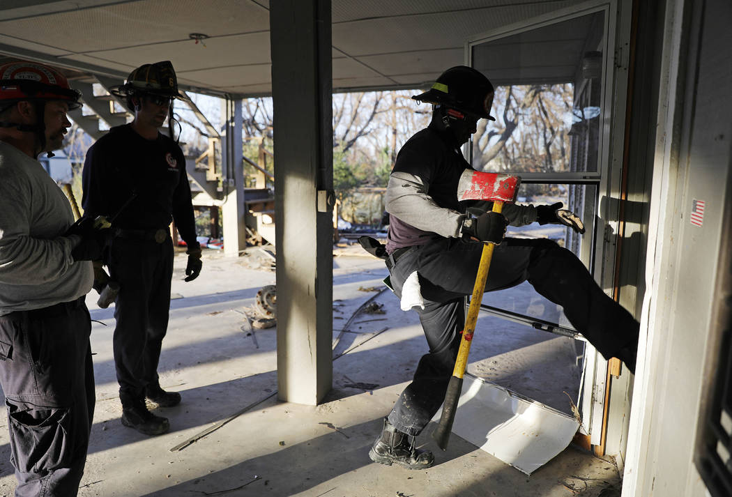 Members of a South Florida urban search and rescue team try to gain entry to a home while looking for survivors of hurricane Michael in Mexico Beach, Fla., Friday, Oct. 12, 2018. (AP Photo/David G ...