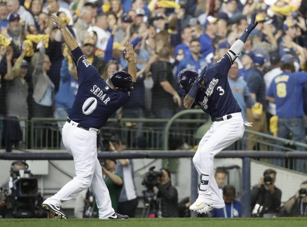 Milwaukee Brewers' Orlando Arcia celebrates his home run with third base coach Ed Sedar during the fifth inning of Game 2 of the National League Championship Series baseball game against the Los A ...