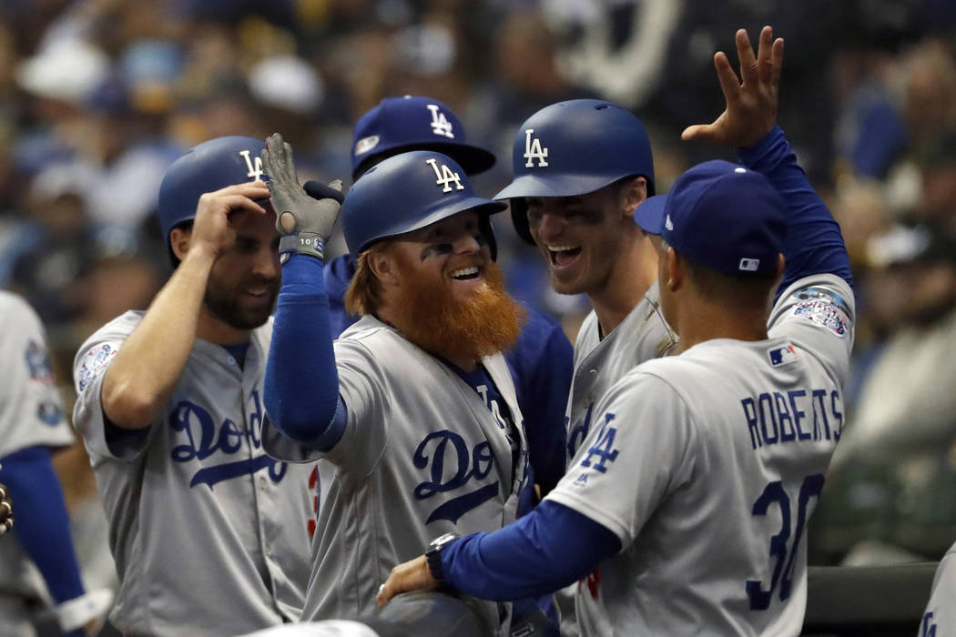 Los Angeles Dodgers' Justin Turner (10) celebrates with manager Dave Roberts (30) after hitting a two-run home run during the eighth inning of Game 2 of the National League Championship Series bas ...