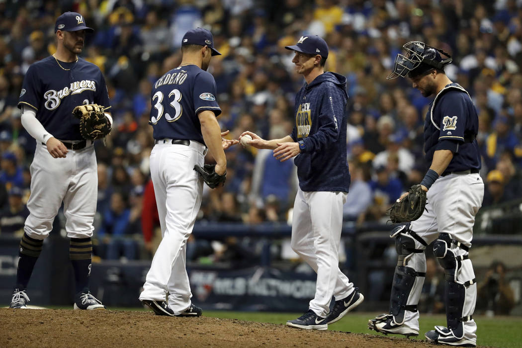 Milwaukee Brewers manager Craig Counsell removes relief pitcher Xavier Cedeno (33) during the ninth inning of Game 2 of the National League Championship Series baseball game against the Los Angele ...