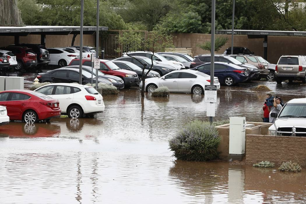 A parking lot full of cars at a business complex is covered with flood waters during a flash flood as a result of heavy rains from tropical storm Rosa Tuesday, Oct. 2, 2018, in Phoenix. (AP Photo/ ...
