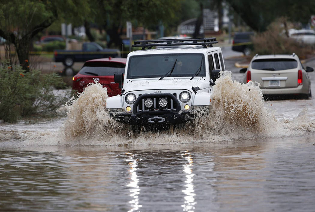 A Jeep drives through a flooded street to get sand bags to deliver to local businesses during a flash flood as a result of heavy rains from tropical storm Rosa Tuesday, Oct. 2, 2018, in Phoenix. ( ...