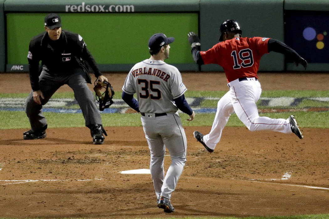 Boston Red Sox's Jackie Bradley Jr., right, scores past Houston Astros starting pitcher Justin Verlander on a wild pitch during the fifth inning in Game 1 of a baseball American League Championshi ...