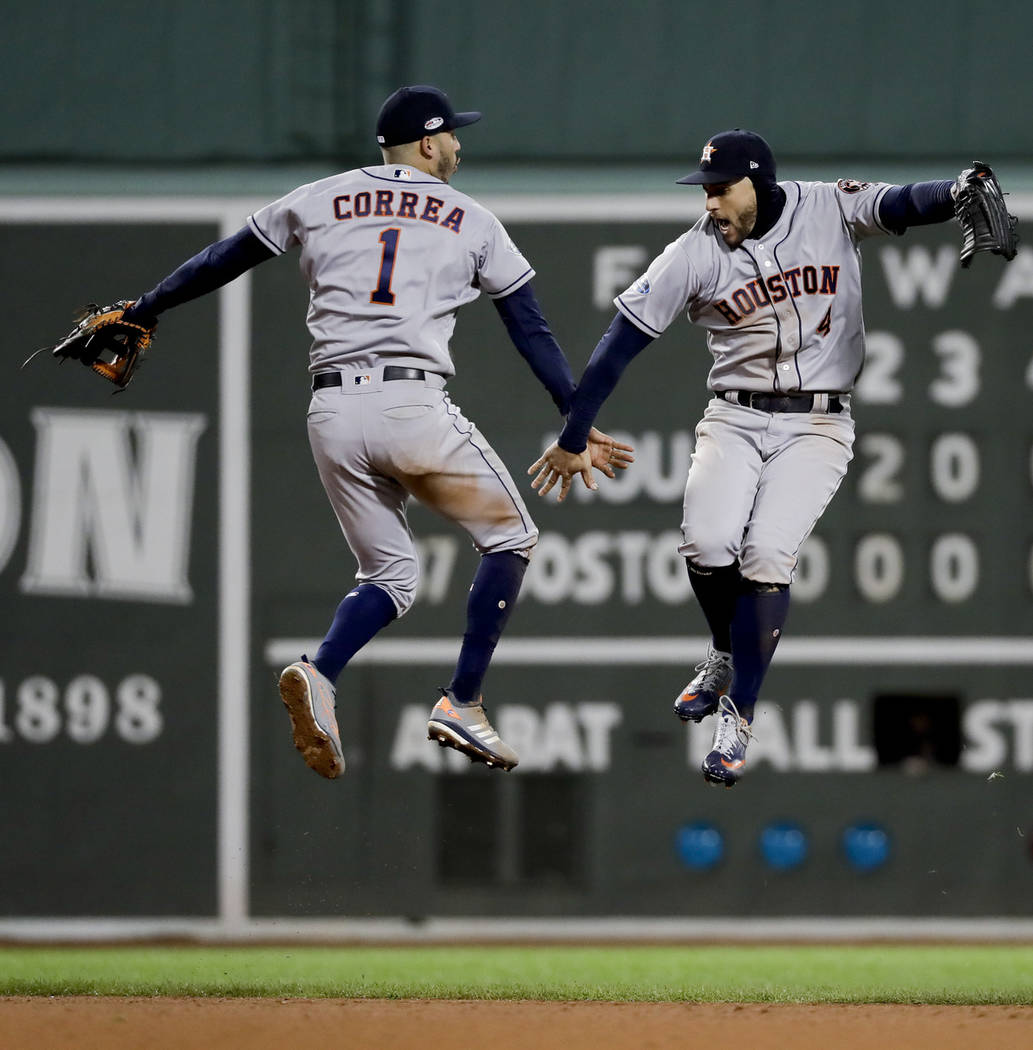 Houston Astros center fielder George Springer, right, and shortstop Carlos Correa celebrate their win against the Boston Red Sox in Game 1 of a baseball American League Championship Series on Satu ...