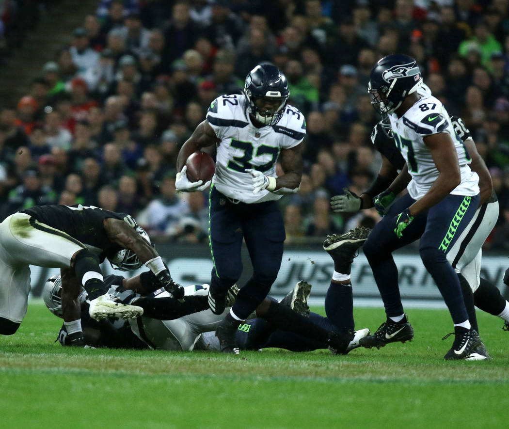 Seattle Seahawks running back Chris Carson (32) runs with the football during the first half of an NFL game against the Oakland Raiders at Wembley Stadium in London, England, Sunday, Oct. 14, 2018 ...