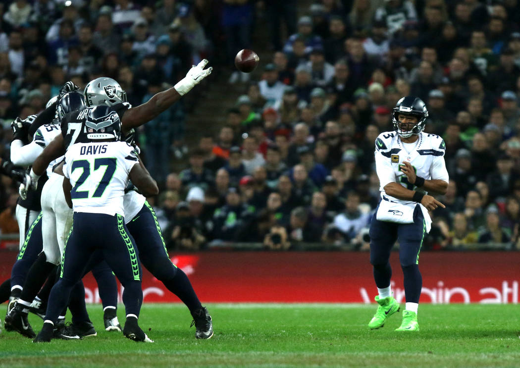 Seattle Seahawks quarterback Russell Wilson (3) throws the football as Oakland Raiders defensive tackle Maurice Hurst (73) tries to deflect it during the first half of an NFL game at Wembley Stadi ...