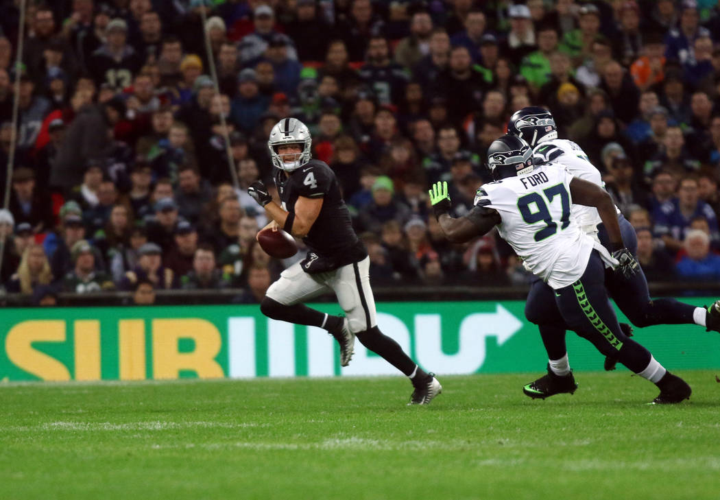 Oakland Raiders quarterback Derek Carr (4) scrambles with the football as Seattle Seahawks defensive tackle Poona Ford (97) and defensive end Frank Clark (55) pursue him during the first half of a ...