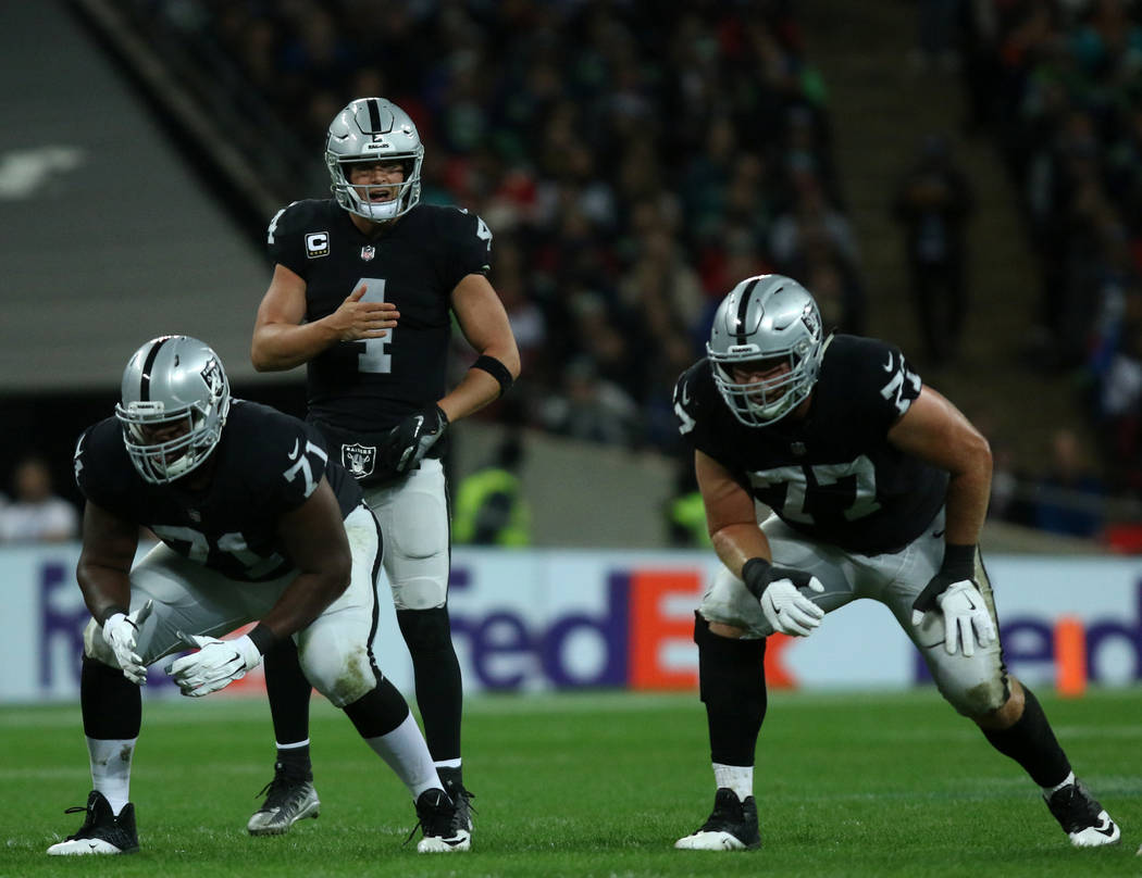 Oakland Raiders quarterback Derek Carr (4) calls a play as offensive tackle Justin Murray (71) and offensive tackle Kolton Miller (77) are set on the line of scrimmage during the first half of an ...