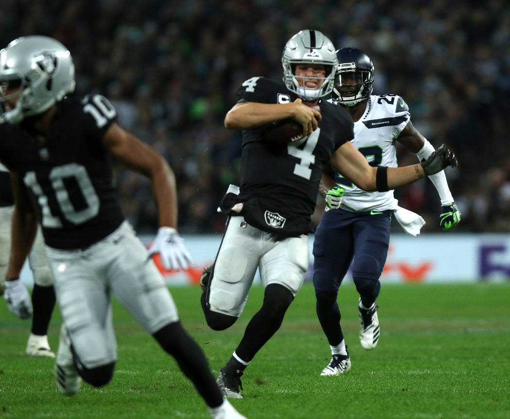 Oakland Raiders quarterback Derek Carr (4) runs with the football during the first half of an NFL game against the Seattle Seahawks at Wembley Stadium in London, England, Sunday, Oct. 14, 2018. He ...