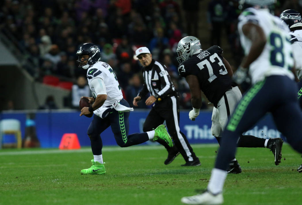 Seattle Seahawks quarterback Russell Wilson (3) scrambles with the football as Oakland Raiders defensive tackle Maurice Hurst (73) pursues him during the first half of an NFL game at Wembley Stadi ...