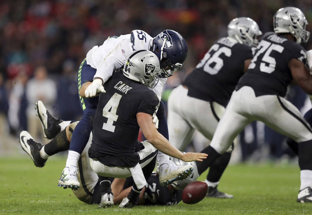 Seattle Seahawks defensive end Frank Clark (55) sacks Oakland Raiders quarterback Derek Carr (4) during the second half of an NFL football game at Wembley stadium in London, Sunday, Oct. 14, 2018. ...