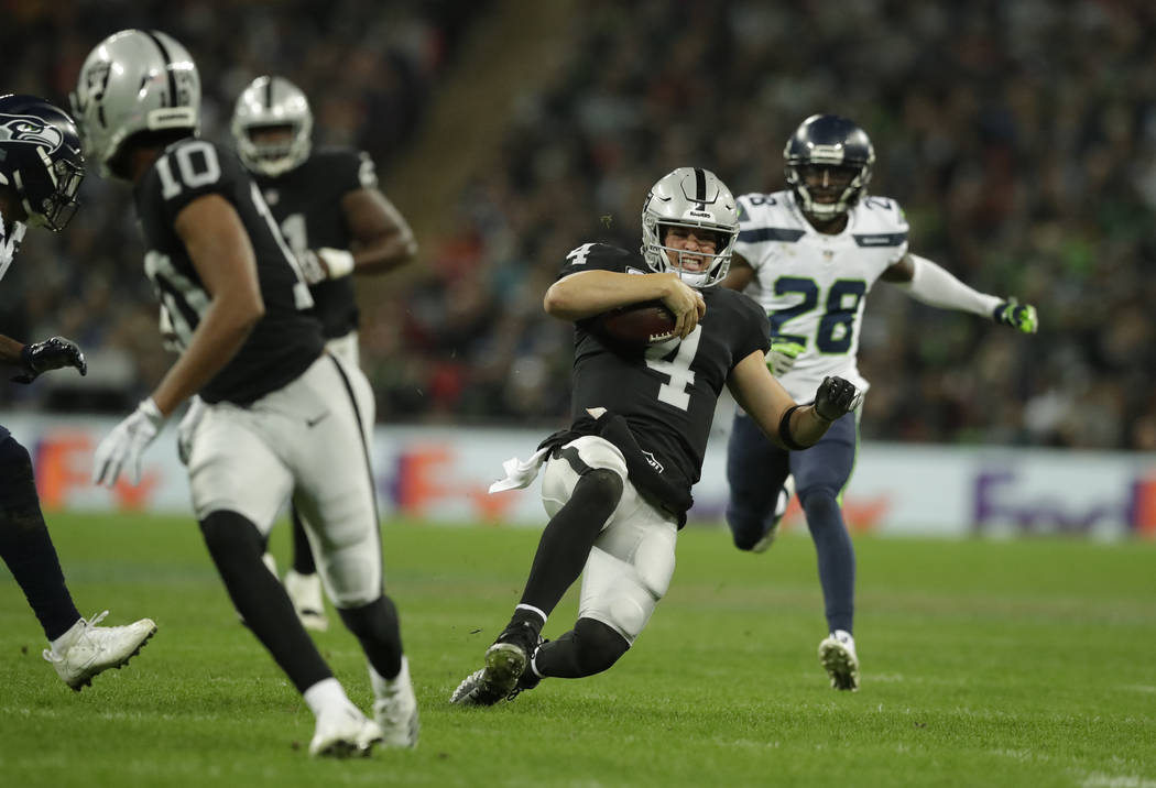 Oakland Raiders quarterback Derek Carr (4) slides after scrambling for yards during the first half of an NFL football game against Seattle Seahawks at Wembley stadium in London, Sunday, Oct. 14, 2 ...