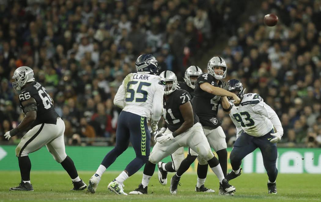 Oakland Raiders quarterback Derek Carr (4), second right, passes the ball during the first half of an NFL football game at Wembley stadium in London, Sunday, Oct. 14, 2018. (AP Photo/Matt Dunham)