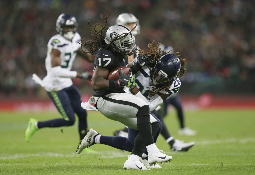 Oakland Raiders wide receiver Dwayne Harris (17), left, is challenged by Seattle Seahawks cornerback Shaquill Griffin (26) during the first half of an NFL football game at Wembley stadium in Londo ...