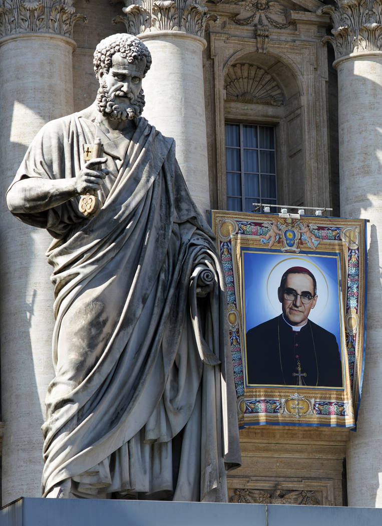 The tapestry of Roman Catholic Archbishop Oscar Romero hangs from a balcony of the facade of St. Peter's Basilica at the Vatican, Saturday, Oct. 13, 2018. Pope Francis will canonize two of the mos ...