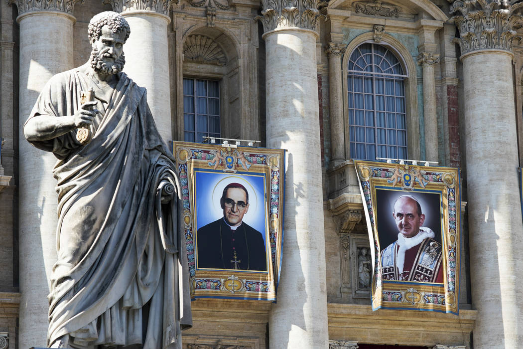 The tapestries of Roman Catholic Archbishop Oscar Romero, left, and Pope Paul VI hang from a balcony of the facade of St. Peter's Basilica at the Vatican, Saturday, Oct. 13, 2018. Pope Francis wil ...