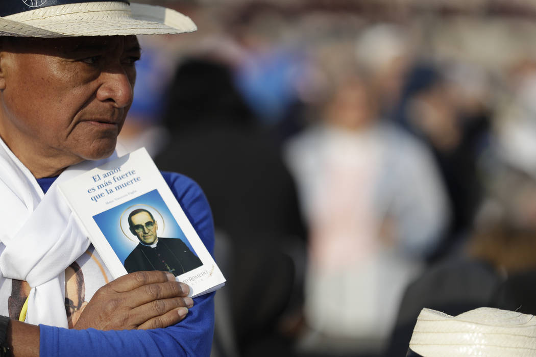 A man holds a picture of martyred Salvadoran Archbishop Oscar Romero prior to a canonization ceremony in St. Peter's Square at the Vatican, Sunday, Oct. 14, 2018. Pope Francis canonizes two of the ...