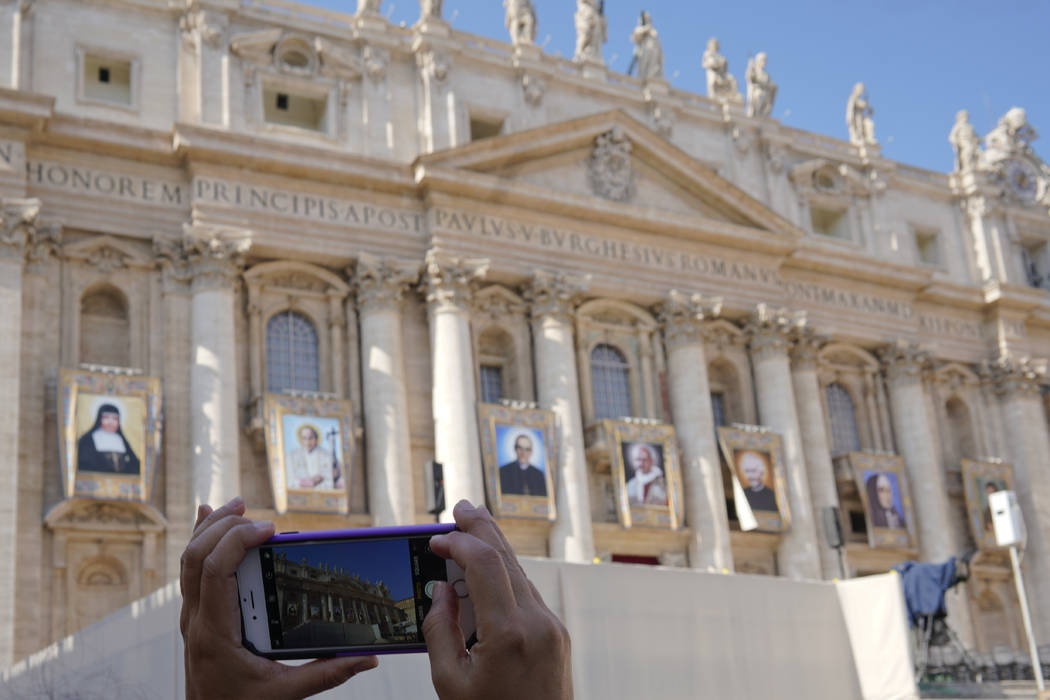 A woman takes photos of tapestries of Roman Catholic Archbishop Oscar Romero, 3rd from left, and Pope Paul VI, 4th from left, hanging from a balcony of the facade of St. Peter's Basilica at the Va ...