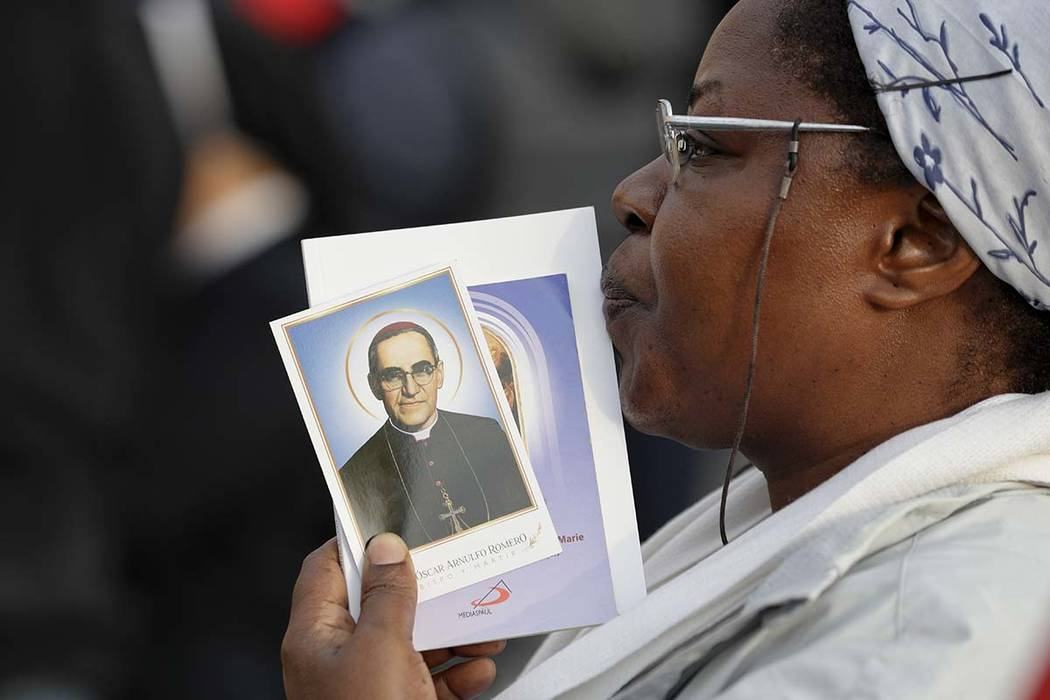 A woman holds a picture of martyred Salvadoran Archbishop Oscar Romero, in St. Peter's Square at the Vatican, Sunday, Oct. 14, 2018. Pope Francis canonizes two of the most important and contested ...